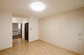 1人部屋の写真。床は明るい色のフローリング、白めの壁、入り口のすぐそばにトイレがある